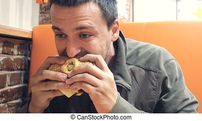 Man eating a cheeseburger at fast food restaurant - A man...