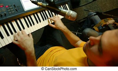 keyboard player playing on synthesizer in recording studio