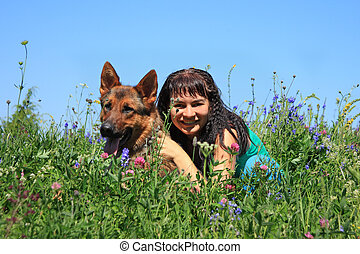 The girl with a dog sit in a grass