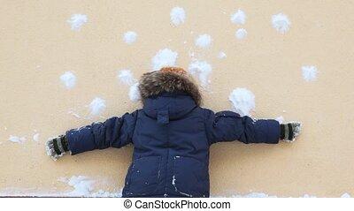 boy stand at wall and at it shoot snowballs