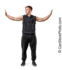 Muscled young man stands pushing invisible walls with his...