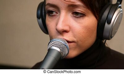 young woman singing through a microphone in studio