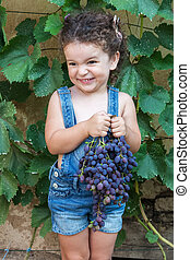 Girl holding bunch of grapes - Cute smiling baby girl holds...