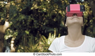 Woman explores virtual reality using VR glasses - Young...