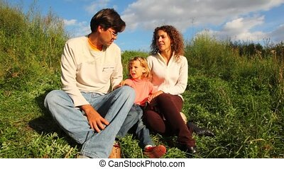 family from mother, father and daughter sits on green herb,...
