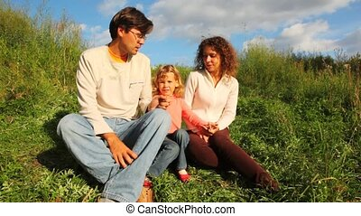 family from mother, father and daughter sits on green hill in park