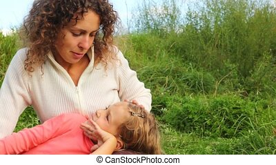 daughter lies beside mom knee on green field and they talk...