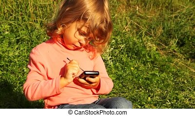 girl sit in park, hold communicator in hands and play in it