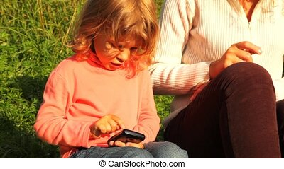 daughter and mother sits green lawn and play in communicator