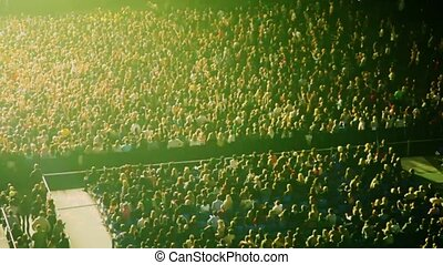 people in light flashes in concert hall
