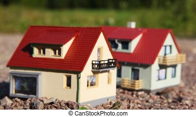 two small toy houses with red roofs stand on stones in park