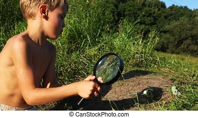 boy burns out magnifying glass leaves on cuteth in park....