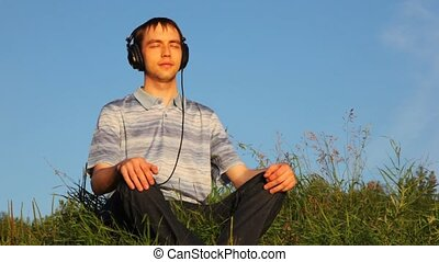 young man sits listening to music in cutephone on glade in...