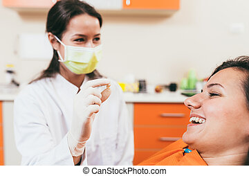 Patient after tooth extraction - Happy dentist holding a...