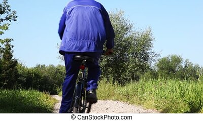 man in turn blue gym suits goes forward on black bicycle in...