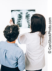 Doctor and patient looking at radiography - Back of female...