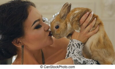 girl holding and kissing rabbit - woman holding and kissing...