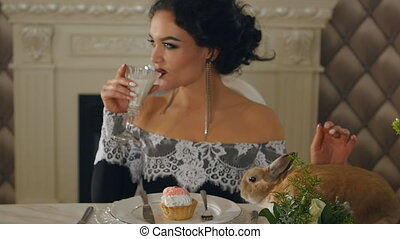 woman in evening dress is drinking milk and stroking a...