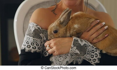 Lady in evening dress holding a rabbit in the hands of