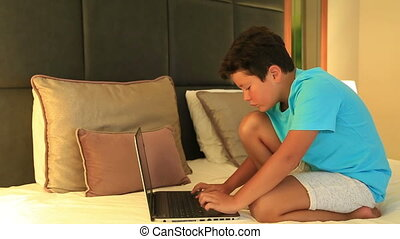 Child doing homework with laptop - School Boy Using Laptop...