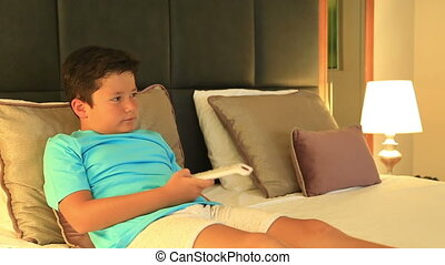Child lying on bed and watching tv - Little boy watching a...