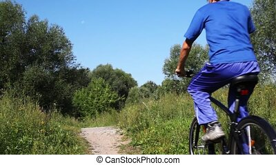man in turn blue gym suits goes forward on black bicycle on footpath in park