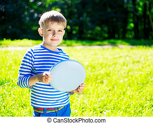 Boy playing frisbee - happy boy playing frisbee outdoor on a...