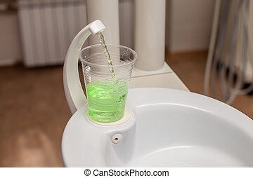 Tooth wash in plastic cup on the sink