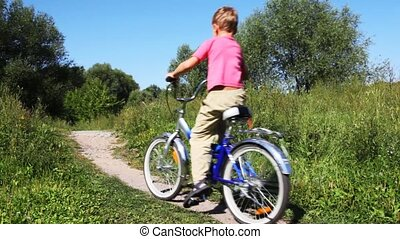 boy in pink vest and man in turn blue sports suit go for drive forward on bicycle on path in park