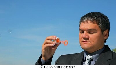 man puffing up soap bubbles blue sky in background