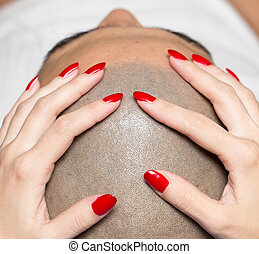 female hand on the man's bald head