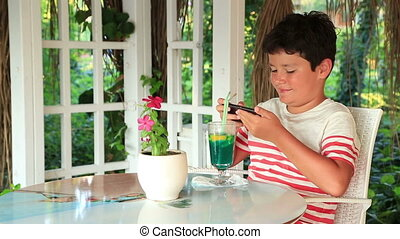 Cute child using smartphone - Young boy gaming on the...