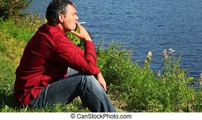 man sitting on bank and smoking