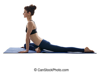 Side view of pretty girl practicing yoga on mat