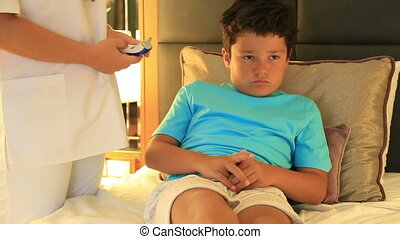 Doctor measuring temperature little boy with ear taking...