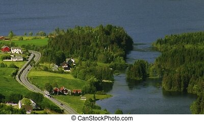 View of green countryside at coast. Road. Little houses. Water. Summer sunny day. Landscape. Nature