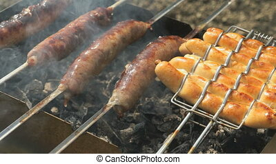 Cooking of grilled sausages on skewers on coals - Cooking of...
