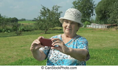 Elderly grandmother takes photos the park - Elderly...
