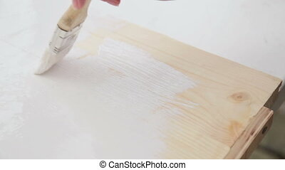 Wood painting with a brush in white color