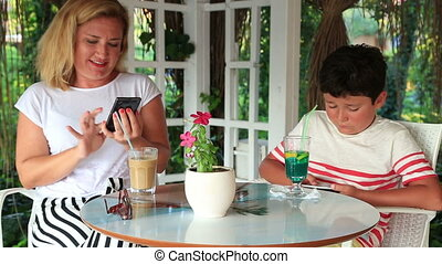 Mother and son with smartphone - Mother with son sitting at...