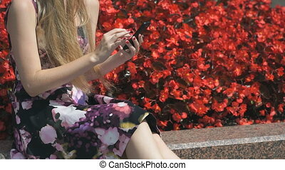 Young girl holds a mobile phone and reads messages - Young...