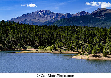 Kayaking and Paddle Boarding on Mountain Lake - Two paddle...