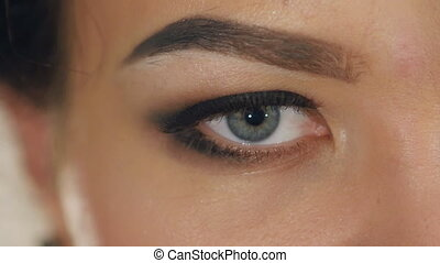 extreme close-up of female eye with a professional make-up in slow motion
