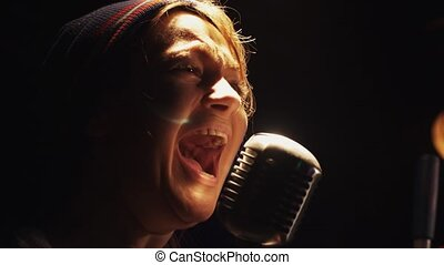 Scrubwoman scream in vintage microphone on stage of club. Dance with mop.