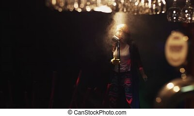 Scrubwoman dance and sing on stage in vintage microphone under spotlight. Smoke