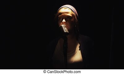 Scrubwoman in hat start sing into vintage microphone on stage of empty club