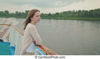 Young beautiful woman standing on deck of cruise ship and looking at river.