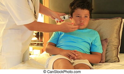 Nurse dripping eardrops to child i - Female doctor or nurse...