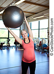 Pregnant women doing stretching exercise - A pregnant woman...