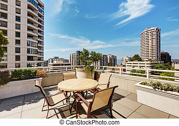 Apartment building roof top terrace exterior with patio table set
